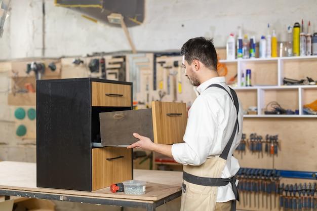 Möbelfabrik, kleinunternehmen und menschenkonzept - junger mann, der in der möbelproduktion arbeitet