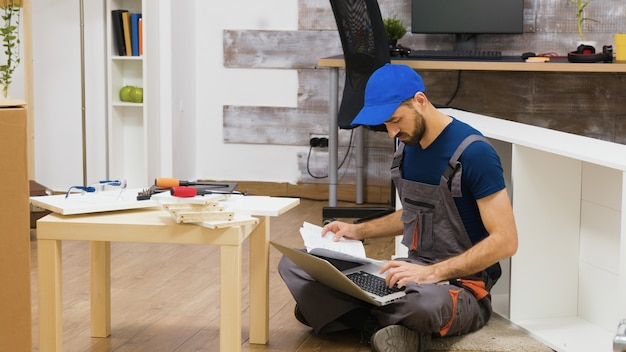 Möbelmontagearbeiter benutzt laptop, um anweisungen zu konsultieren. handwerker macht einen guten job.