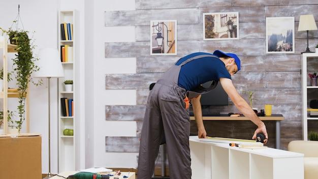 Möbelmontagearbeiter, der anweisung zum lesen steht und ein maßband verwendet. arbeiterwerkzeuge.