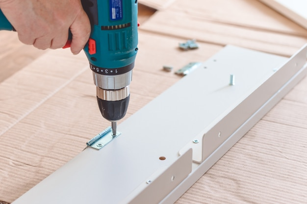 Möbelmontageteile und werkzeuge für selbstmontagemöbel auf dem boden.
