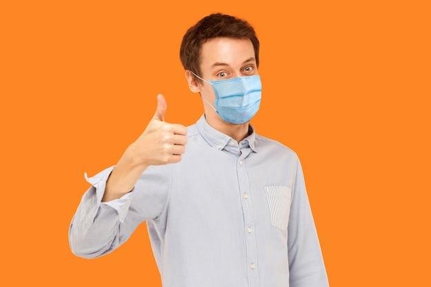 Mögen. porträt eines zufriedenen jungen arbeitermannes mit chirurgischer medizinischer maske, der daumen hoch steht und die kamera lächelnd betrachtet. indoor-studioaufnahme auf orangem hintergrund isoliert.