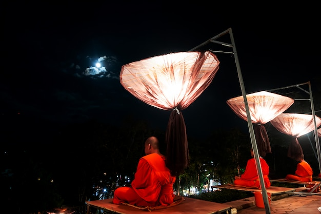 Mönche beten in loy krathong festival mit himmelslaternen, fliegende laternen