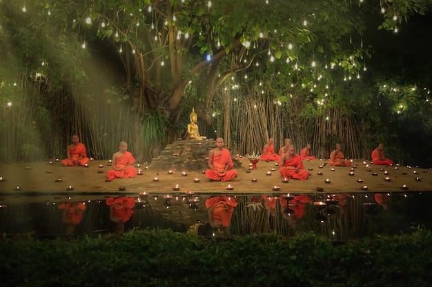 Mönche meditieren am ufer mit schönen lichtern und kerzen