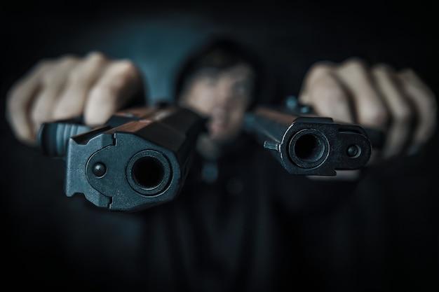 Mörder auf schwarzem hintergrund zwei pistolen in den händen des mannes sind auf die kamera gerichtet, nahaufnahme von zwei pistolenmuzz...