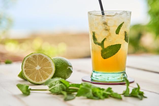 Mojito bereit, mit dem strand im hintergrund zu trinken. trinkkonzept für den sommer.