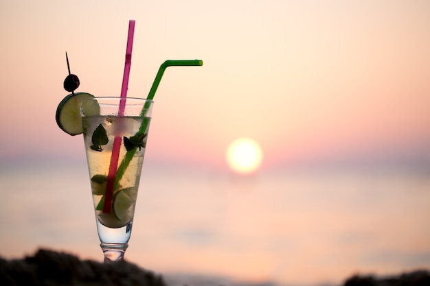 Mojito-cocktail am strand bei sonnenuntergang