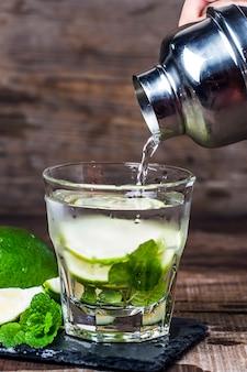 Mojito-cocktail in einem bohrer auf einem rustikalen tisch, selektiven fokus
