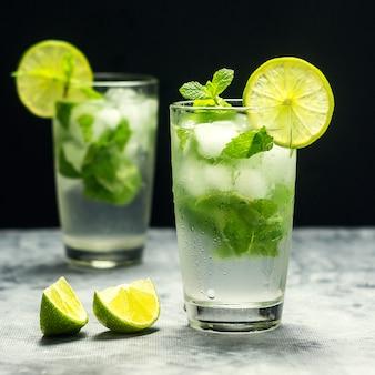 Mojito-cocktail mit kalk und minze im glas auf einem grauen stein. quadrat
