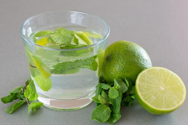 Mojito-cocktail mit limette und minze im glas an einer grauen wand