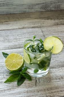 Mojito-cocktail mit limette und minze im highballglas auf einem weißen holztisch