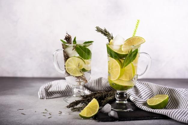 Mojito-cocktail mit limette und minze im highballglas auf grauem steinhintergrund