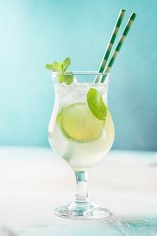 Mojito-cocktail mit limette und minze in einem blauen hintergrund des cocktailglases.
