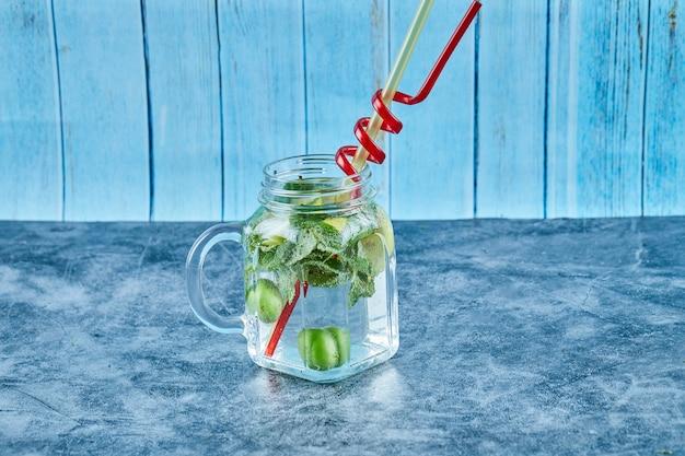 Mojito-cocktail mit limetten- und minzscheiben auf blauem tisch