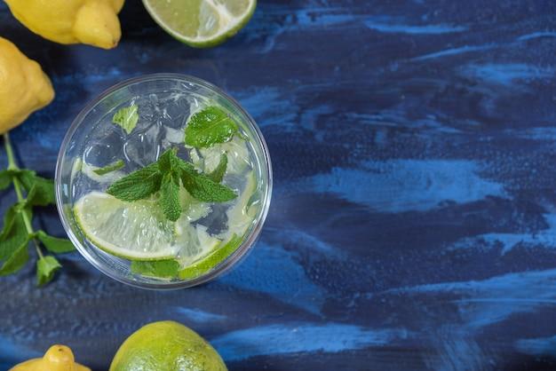 Mojito-cocktail mit seinen bestandteilen auf einer blauen tabelle