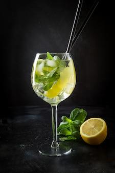 Mojito cocktail oder limonade mit minze im glas auf schwarzem abschluss herauf sommergetränk