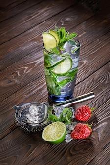 Mojito-getränk mit limette und minze im glas mit eiswürfeln auf hölzernem hintergrund