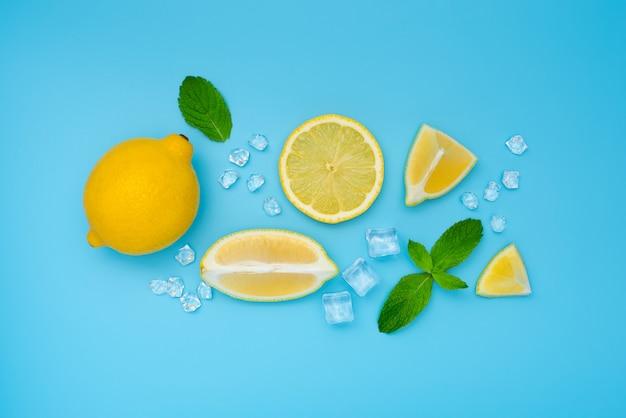 Mojito-zitrone auf blauem tisch. zitrone, eis und minze liegen flach. konzept: sommer erfrischender cocktail.