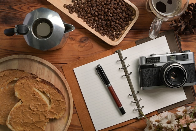 Moka-topf, notebook, kamera und erdnussbutter-sandwich auf holztisch.