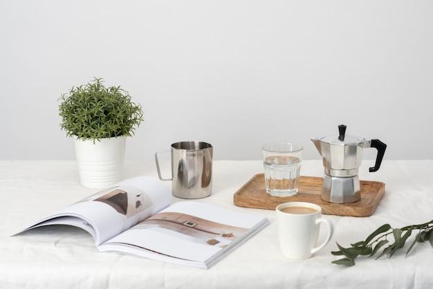 Moka und glas wasser auf dem hölzernen tablett, pflanze im topf, zeitschriften