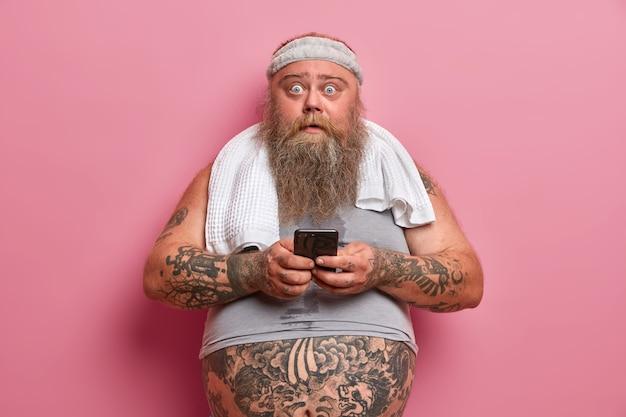 Molliger schockierter mann mit dickem bart, der mit sporttraining beschäftigt ist und sportbekleidung trägt. er kümmert sich um sein gewicht. er verwendet ein mobiltelefon, um zu überprüfen, wie viel kalorien verbrannt wurden. sport, motivation