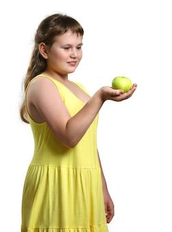 Molliges lächelndes mädchen im gelben sommerkleid hält grünen apfel in der hand und schaut ihn an