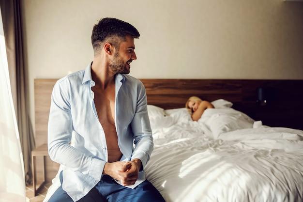 Moment nach dem liebesspiel und kuscheln im hotelzimmer. der mann sitzt auf dem bett und lächelt die frau an, zieht einen business-anzug an. eine frau sieht ihren geliebten mit viel leidenschaft an und liegt auf dem bett.