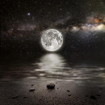 Monat auf einem hintergrundsternhimmel, der im meer reflektiert wird. elemente dieses von der nasa bereitgestellten bildes