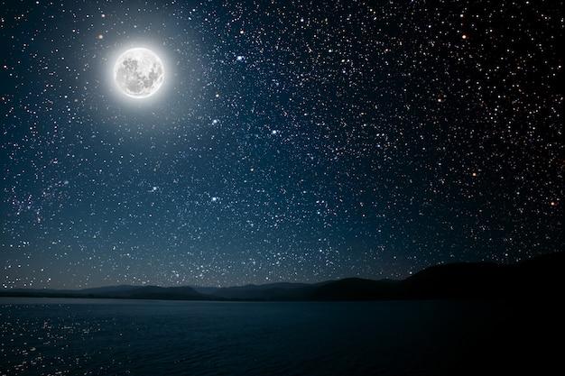 Mond gegen einen hellen nächtlichen sternenhimmel, der sich im meer spiegelt.