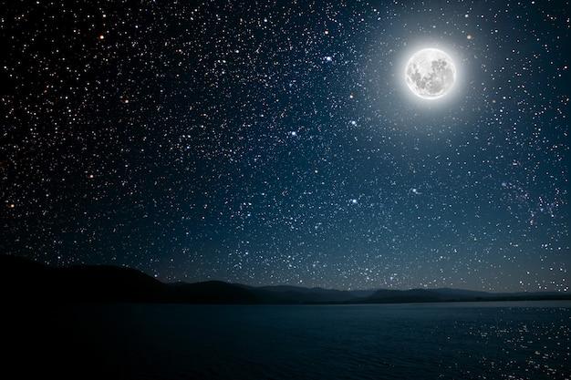 Mond gegen einen sternenklaren himmel der hellen nacht, der im meer reflektiert wird.