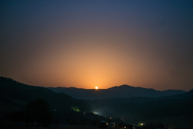Mondaufgang am nachthimmel mit vielen sternen über der bergkette Premium Fotos