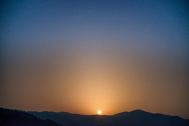 Mondaufgang am nachthimmel mit vielen sternen über der bergkette