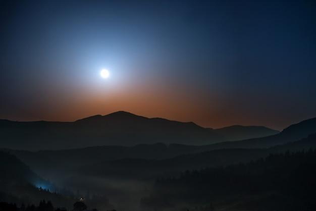Mondaufgang über den bergen in der nacht mit sternen und dunkelblauem himmel