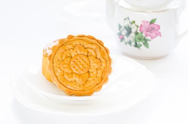 Mondkuchen des blumenentwurfs über weißen platten, zum des chinesischen mondfestivals zu feiern