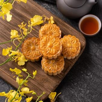 Mondkuchen, mondkuchen für mittherbstfest, konzept des traditionellen festlichen essens auf schwarzem schiefertisch mit tee und gelber blume, nahaufnahme.
