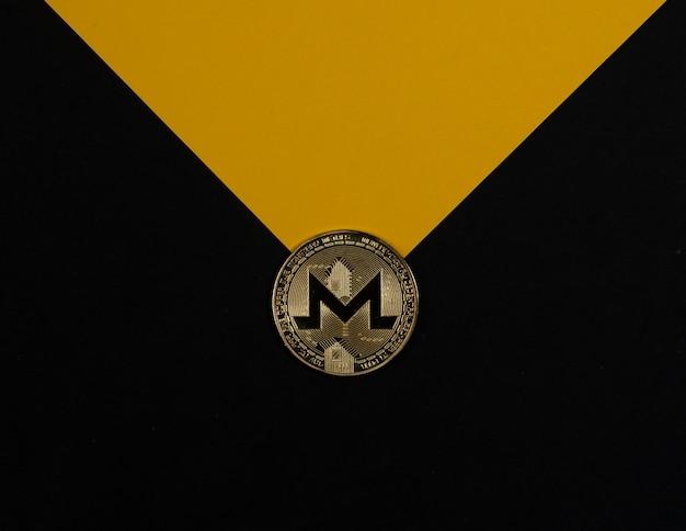 Monero goldene münze auf schwarzem und gelbem hintergrund wie umschlag. kryptowährung und kryptoinvestition.