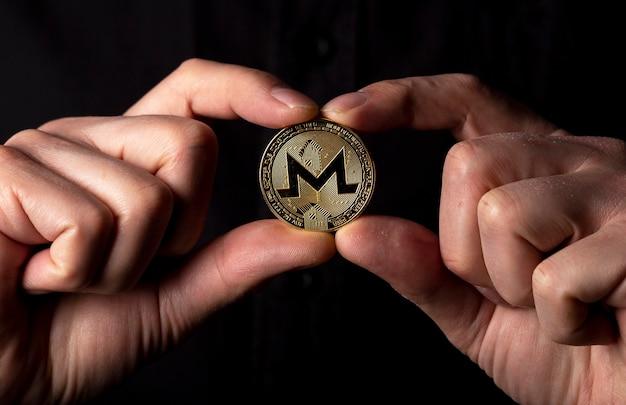 Monero goldene münze in der männlichen hand über schwarzem hintergrund. banner mit kopienraum für text.