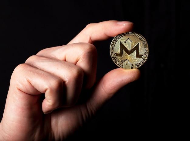 Monero goldene münze in der männlichen hand über schwarzem hintergrund.