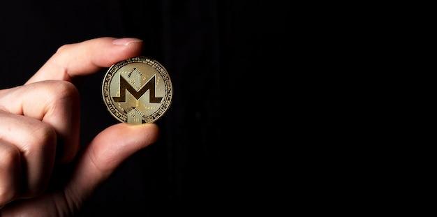 Monero goldene münze in der männlichen hand über schwarzem hintergrundbanner mit kopienraum für text