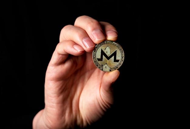 Monero goldene münze in männlicher hand über schwarzem hintergrund