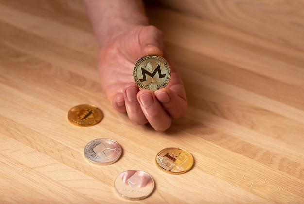 Monero-goldmünze in männlicher hand und andere kryptowährung