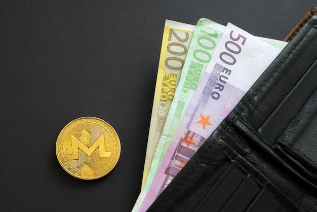 Monero-münze neben euro-banknoten, die aus einer brieftasche auf schwarzer oberfläche herausragen.