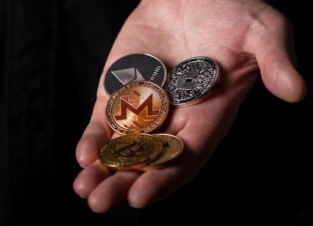 Monero und andere dofferente kryptowährungsmünzen in männlicher hand über schwarzem hintergrund, nahaufnahme.