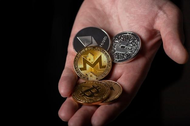 Monero und andere dofferente kryptowährungsmünzen in männlicher hand über schwarzer hintergrundnahaufnahme