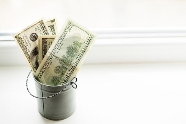 Moneybox, dollar im eimer auf weißem fenster heller hintergrund