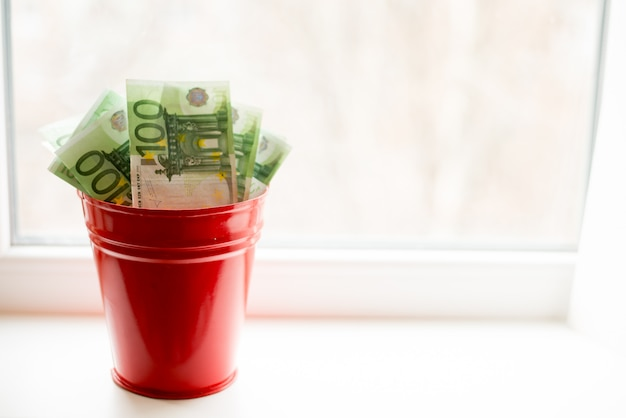 Moneybox, eurorechnung im eimer auf weißem fenster heller hintergrund