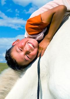 Mongolischer junge mit seinem pferd.