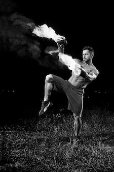 Monochrome aufnahme eines hemdlosen, muskulösen, starken jungen männlichen boxers, der im freien mit seinen boxhandschuhen praktiziert, die mit feuer brennen, brennen, feurige kraft, selbstvertrauen, martialischer kampf fit, muskeln schwitzen agil.