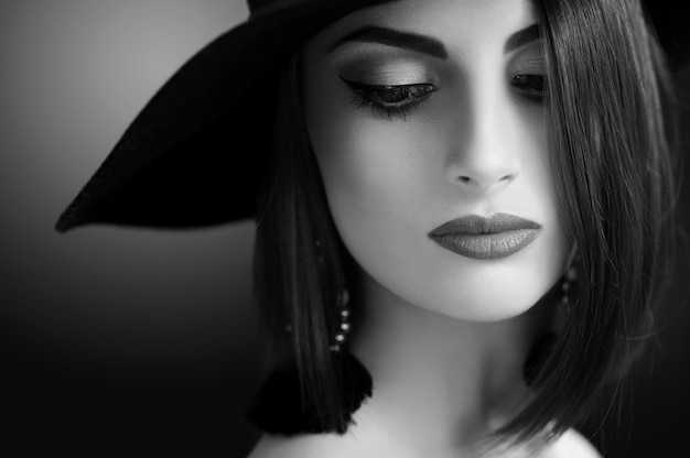 Monochrome nahaufnahme eines wunderschönen jungen stilvollen weiblichen modemodells, das sinnlich mit professionellem make-up und einem hut schönheitskosmetik lippen haut augen frisur outfit retro-vintage-konzept posiert.