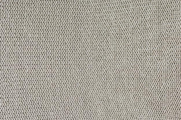 Monochrome textur des strickens. schöner hintergrund mit schleifen. das strickprodukt ist hellbeige.