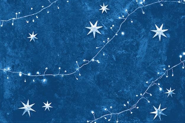 Monochrome wohnung lag auf dunklem strukturiertem brett. draufsicht, flach liegend mit lichtern auf weihnachtslichtgirlande, goldenen kugeln und sternen.